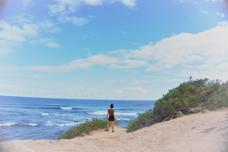 Woman standing at the edge of the sand looking out at the sea from above