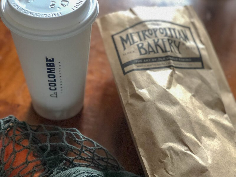 Coffee cup from La Calombe and loaf of bread in brown paper bag from Metropolitan bakery on table