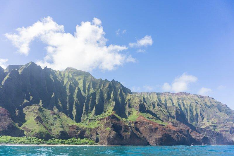 Napali coast green cliffs blue sky on pacific ocean