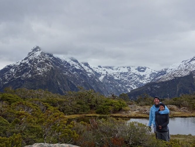 Joe & Alicia from Miles Less Traveled in New Zealand with mountain backdrop