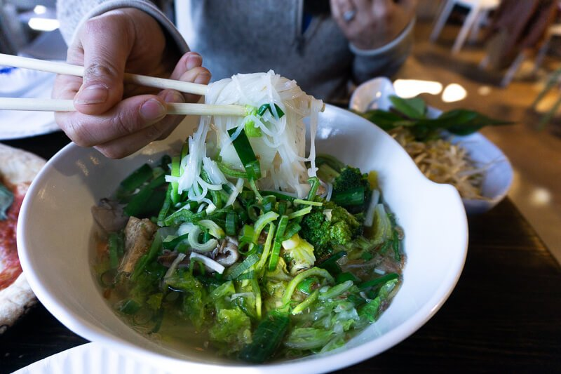 Pho noodles being pulled up from bowl by chopsticks from Saigon Noodle Bar Market at the Fareway