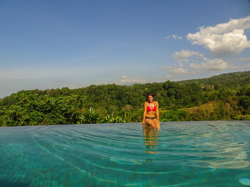 Woman sitting in infinity pool with forest behind