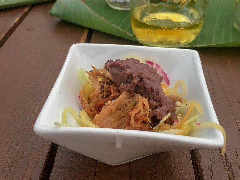 Shredded papaya sald in square bowl with roasted local pig and smashed taro root