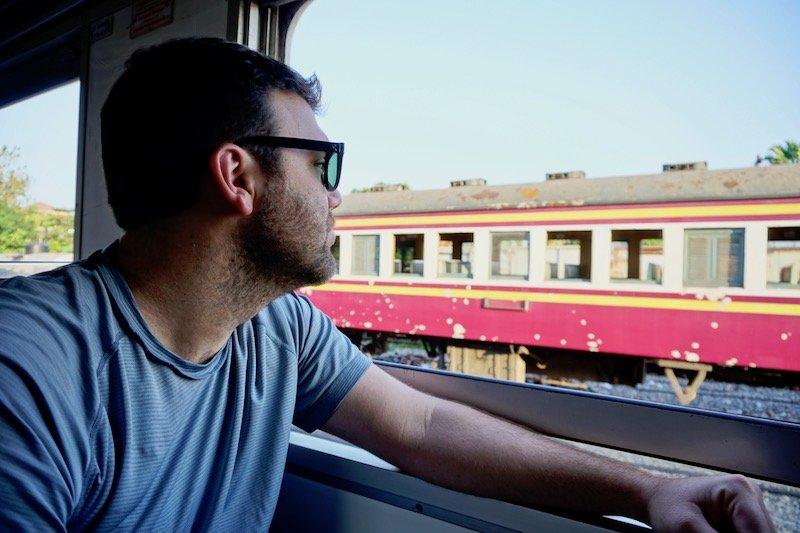 Man looking outside Thai train