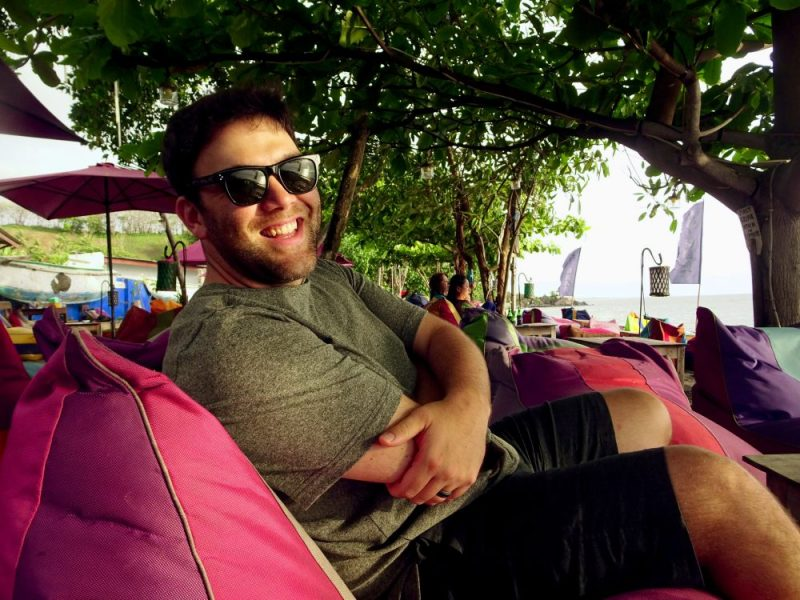 Man on red couch with sunglasses on and arms crossed at beach bar in Indonesia
