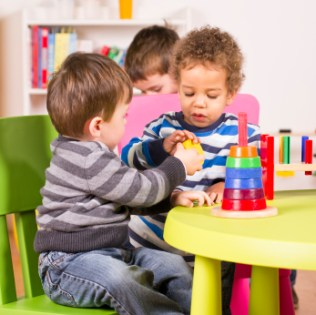 A stock photo of a caucasian and african american child sharing in the play room