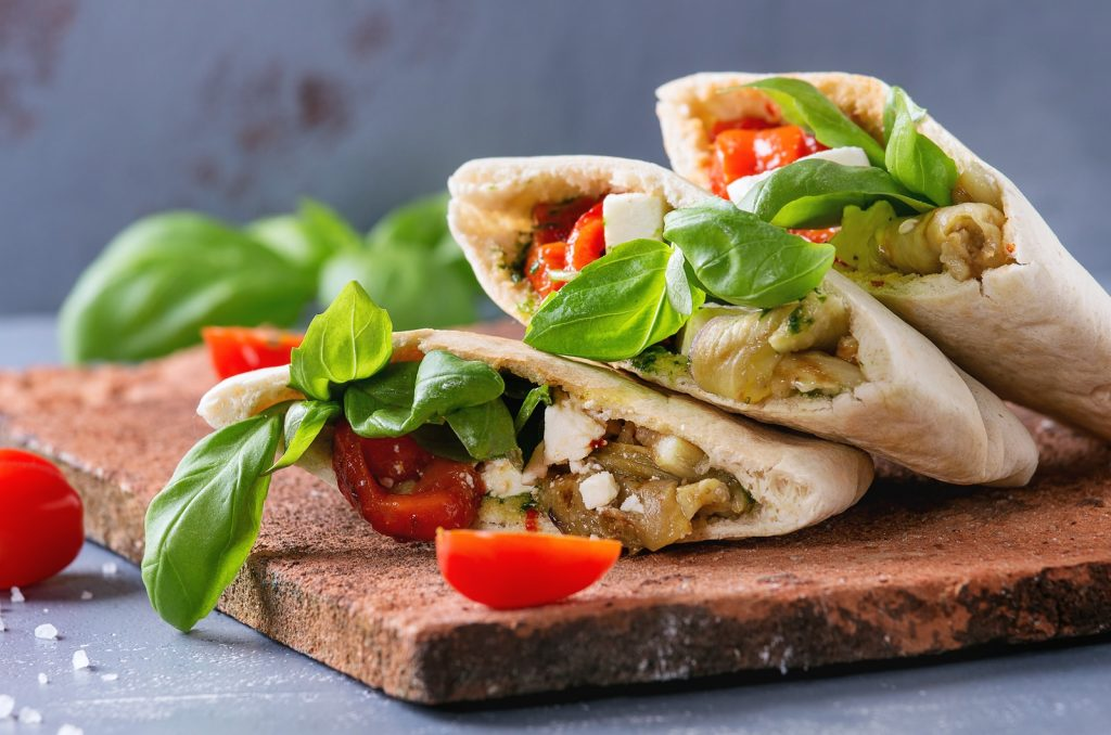 Pita bread sandwiches with grilled vegetables paprika, eggplant, tomato, basil and feta cheese served on terracotta board over gray stone background. Close up. Healthy fast food concept.