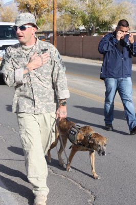 Man in camo with service dog in parade