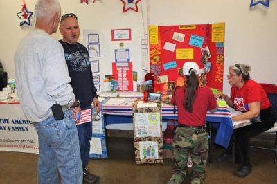 2 men talking and 2 women talking, one kneeling in front of postcard project boards