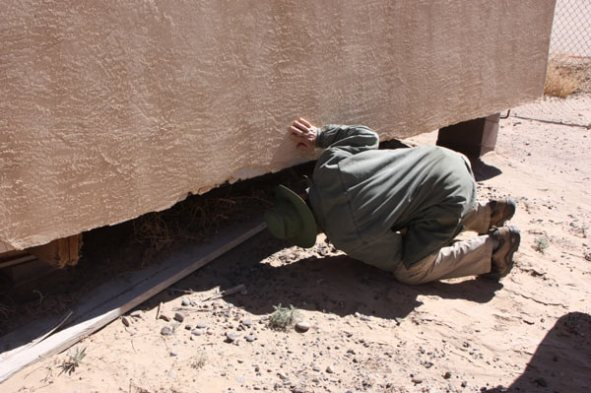 Man with hat checking underneath adobe house on blocks
