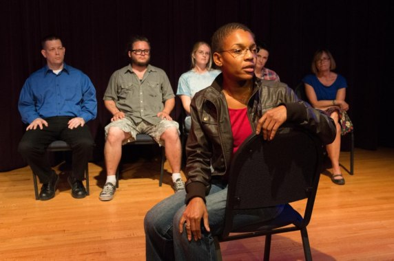 Woman sitting on chair on stage with people seated in background. Telling Project