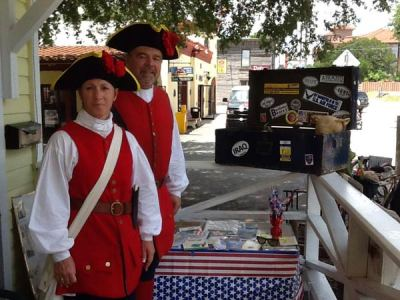 Man and woman dressed in red colonia outfits with Operation Footlocker