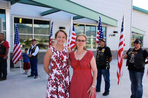 Circe Olson Woessner and woman in flowered dress in front of Flag line Sacrifice & Service 2014