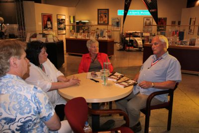 Two men and two women at round table in front of museum exhibit