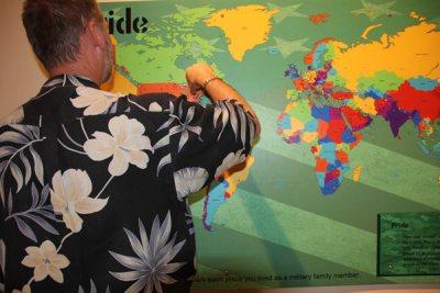 Gentleman in flowered shirt pinning pin to map