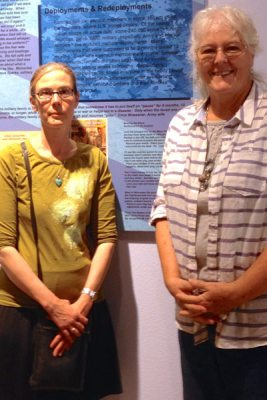 Circe Olson Woessner and woman at Sacrifice & Service exhibit