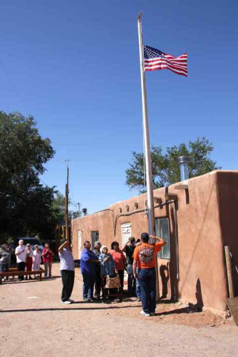 People saluting flag in front of Jemez home