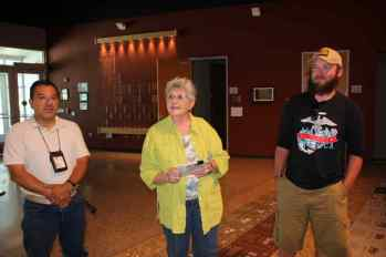 Woman in yellow shirt and two men standing in lobby of Nuclear Museum