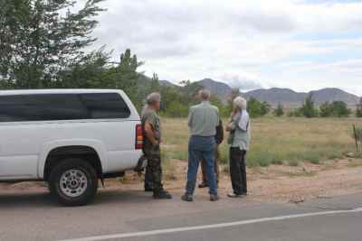 Allen Olson with two other men by car looking at land