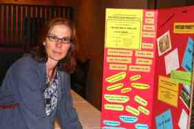 Circe Olson Woessner setting up red poster on table