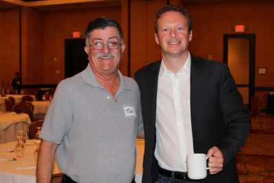 Two men standing together, one with coffee cup