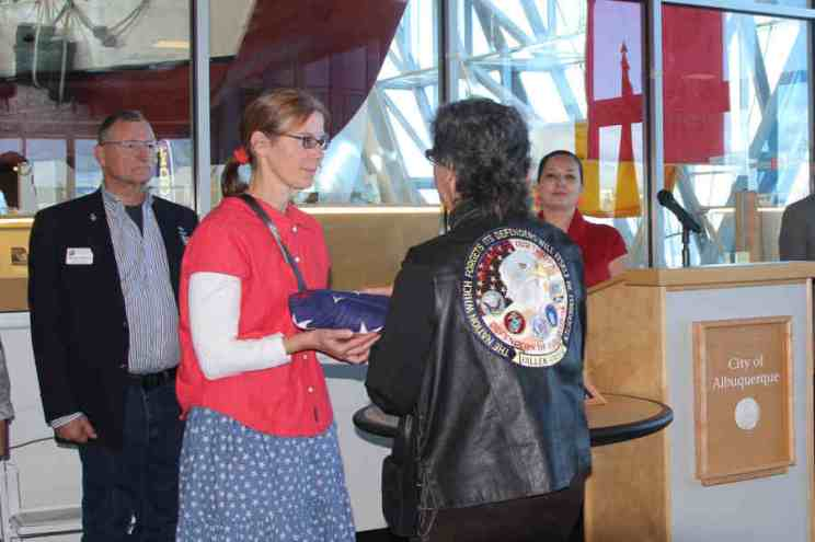 Circe Olson Woessner accepting folded flag