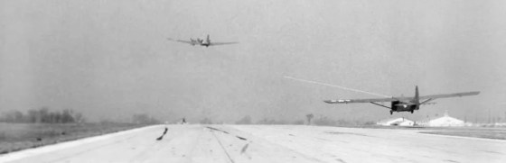 An American-made CG-4 Waco glider is towed into the air by a C-47 Skytrain.