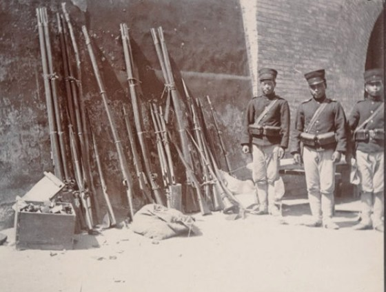 Chinese troops stand beside a cache of wall guns in 1900.