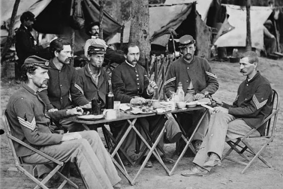 "Soldiers of the 93rd New York Infantry ""enjoy"" a meal consisting of hard-tack.  The rock-hard biscuits were a much-despised staple for troops on both sides of the Civil War. Image courtesy of WikiCommons. (Public Domain)"
