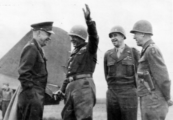 Patton (arm raised) confers with Eisenhower (left) while generals Omar Bradley and Courtney Hodges look on. (Image source: WikiCommons)