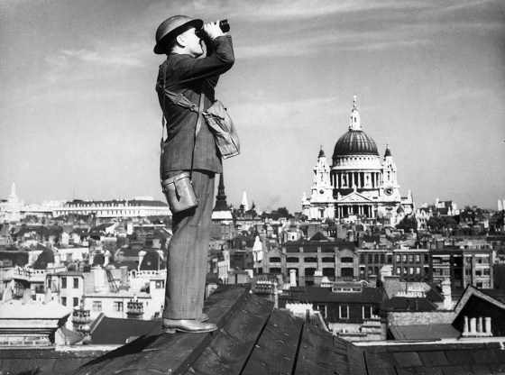 An air defence volunteer scans the skies over London for enemy aircraft. By May of 1941, Hitler called off his bombers. (Image source: WikiCommons)