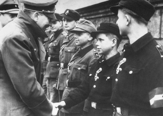 Hitler briefly emerges from his bunker in war-torn Berlin to award Iron Crosses to the last defenders of his Thousand-Year Reich. (Image source: Public Domain)