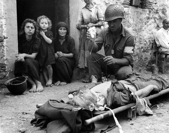 A U.S. Army medic tends to a wounded GI during the Sicily campaign, 1943. (Image source: WikiCommons)