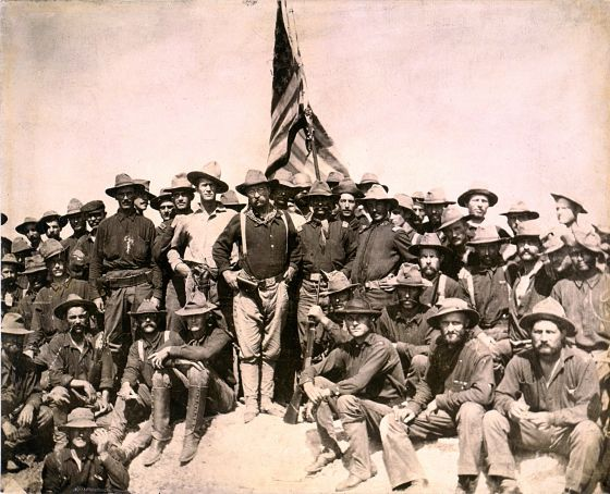 Roosevelt and the Rough Riders stand triumphantly on the high ground commanding the field. (Image source: WikiCommons)