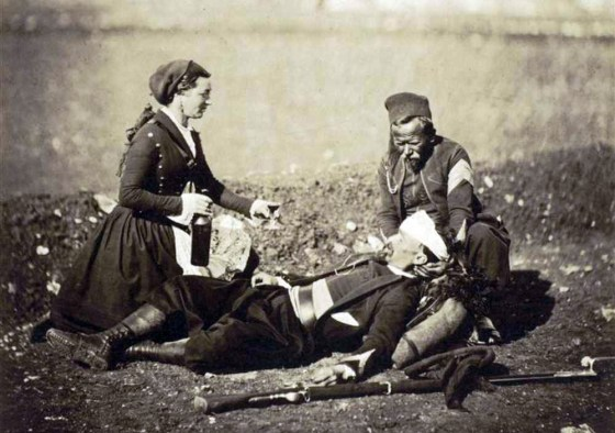 A nurse tends to a wounded soldier.