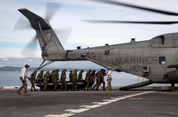 "Japan Ground Self-Defense Force soldiers load a combat rubber raiding craft aboard a CH-53E Super Stallion, assigned to the ""Flying Tigers"" of Marine Heavy Helicopter Squadron (HMH) 361, on the flight deck of the amphibious transport dock ship USS Somerset (LPD 25) during Exercise Iron Fist 2019.  (U.S. Navy photo by Mass Communication Specialist 2nd Class Devin M. Langer)"