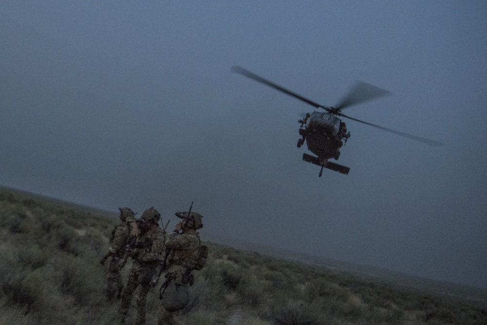 An HH-60G Pave Hawk helicopter flies above Special Tactics Airmen with the 17th Special Tactics Squadron during Jaded Thunder at Mountain Home Air Force Base, Idaho, Aug. 20, 2018. Special Tactics is U.S. Special Operation Command's tactical air and ground integration force, and the Air Force's special operations ground force, leading global access, precision strike, personnel recovery and battlefield surgery operations. (U.S. Air Force photo by Tech. Sgt. Sandra Welch)
