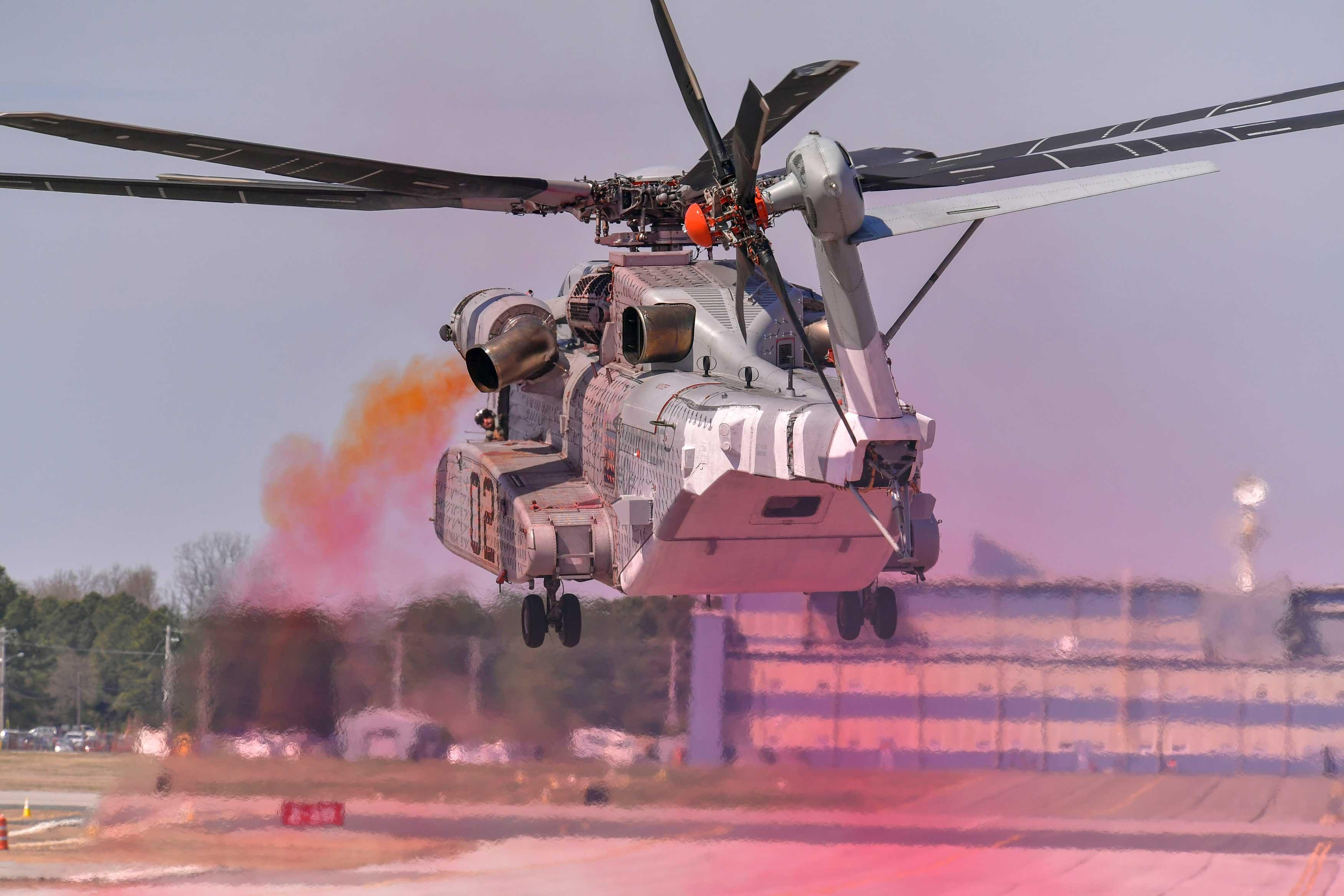 "Colored oil smoke indicates rotor wake and wind effects while external ""tufts"" adhere to the outside of the CH-53K King Stallion showing surface airflow. These efforts validate a modification mitigating Exhaust Gas Re-ingestion for the new Marine Corps aircraft. US Navy photo."