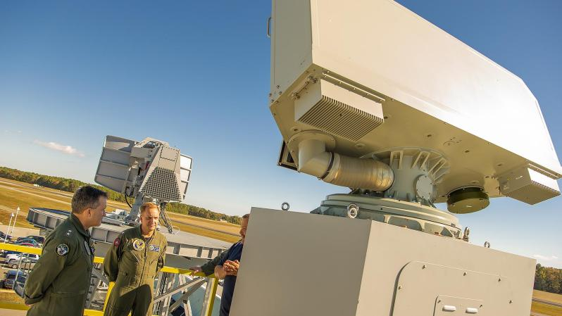 Rear Adm. Shane Gahagan, Program Executive Officer for Program Executive Office Tactical Aircraft Programs (PEO(T)) (left), and Capt. Kevin Watkins, Naval Air Traffic Management Systems Program Office (PMA-213) program manager (center), see a new Shipboard Air Traffic Radar, AN/SPN-50, that is being used for the radar's engineering and manufacturing development phase during a demonstration at Naval Air Warfare Center Aircraft Division Webster Outlying Field on Oct. 23, 2019.