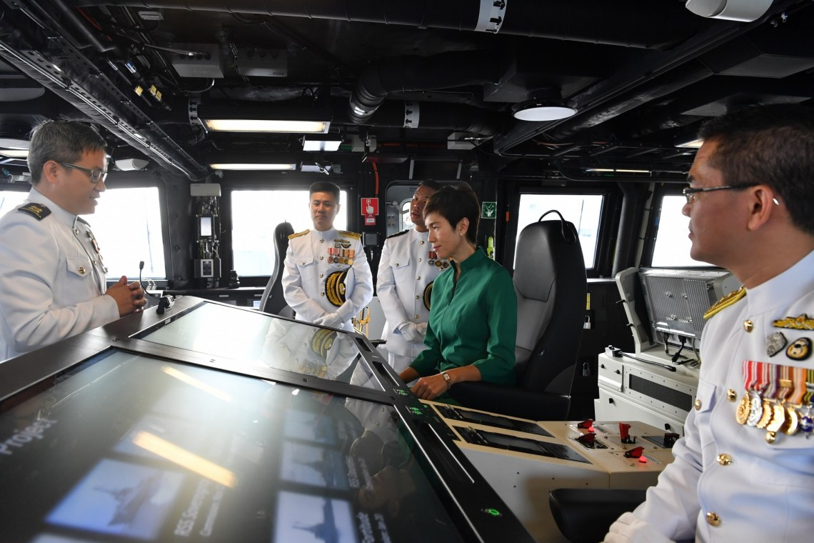 Minister Josephine Teo receiving a brief at RSS Dauntless' Integrated Command Centre, accompanied by the Chief of Navy Rear-Admiral Lew Chuen Hong
