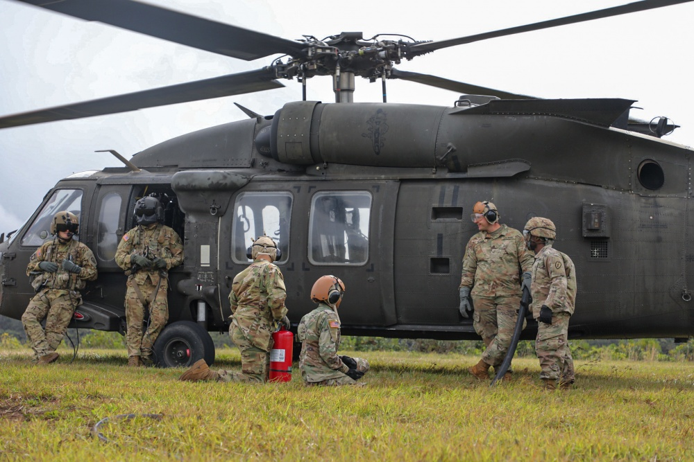 Petroleum Supply Specialists work together to refuel three Black hawksduring training in FATCOW procedures.