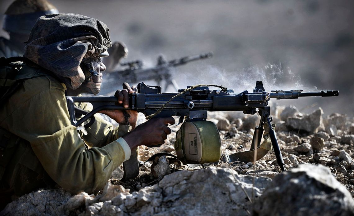 Israeli Defense Forces infantry soldier fires a Negev light machine gun during training.