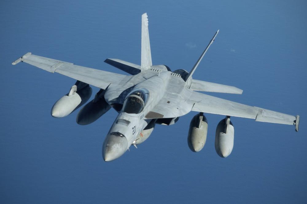A U.S. Navy F/A-18 Super Hornet flies away over the Pacific Ocean near the coast of Brisbane, Australia.