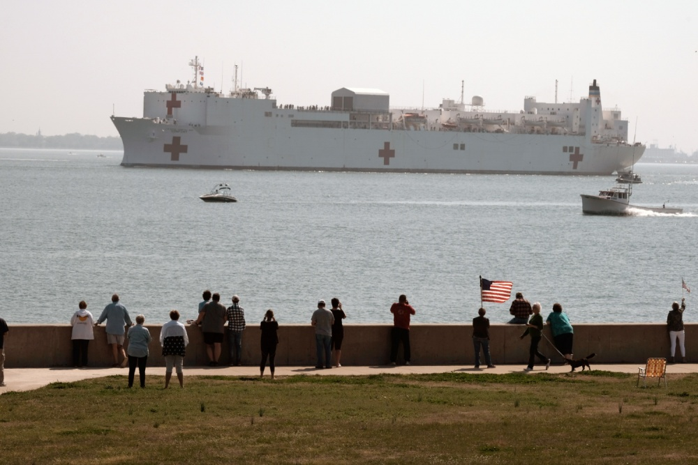 People gather to watch the Military Sealift Command hospital ship USNS Comfort (T-AH 20) depart Naval Station Norfolk, Va. March 28, 2020. (U.S. Navy photo by Mass Communication Specialist 1st Class Joshua D. Sheppard)