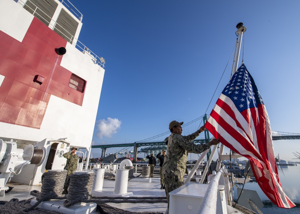 Logistics Specialist 1st Class Tavares Littleton, from Chicago, raises the National Ensign during morning colors aboard the hospital ship USNS Mercy (T-AH 19).   (U.S. Navy photo by Mass Communication Specialist 2nd Class Ryan M. Breeden)