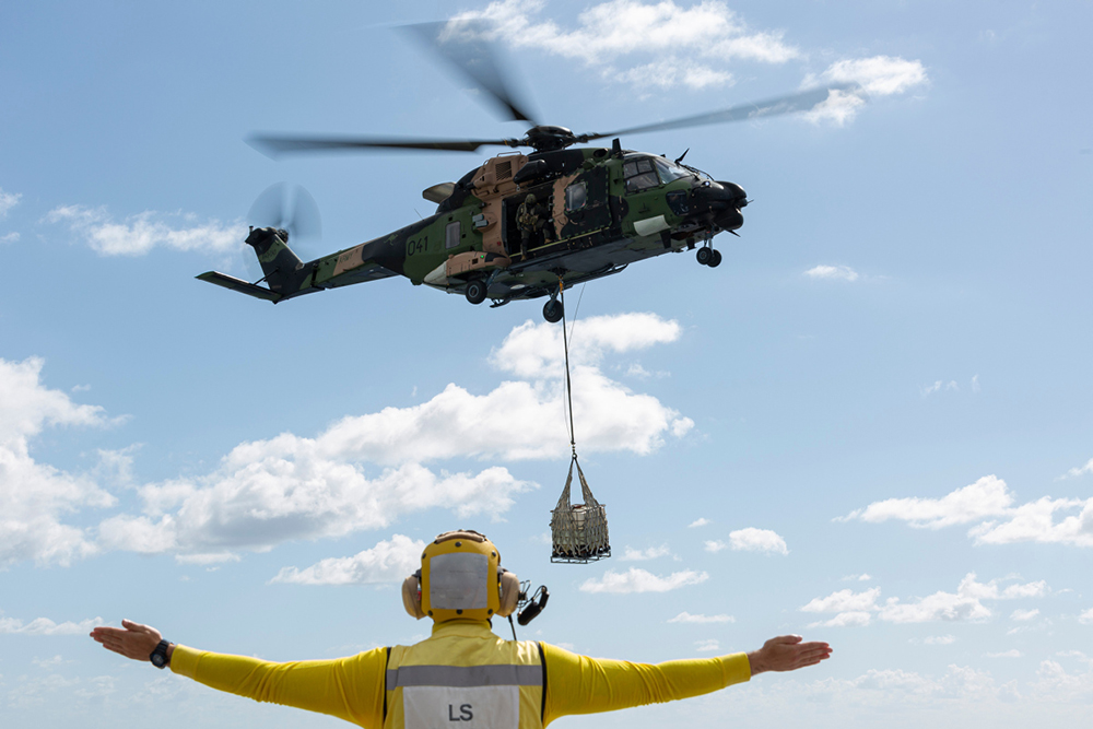 Leading Seaman Aviation Support Blake Dare marshals an MRH-90 helicopter during a vertical replenishment exercise onboard HMAS Adelaide.