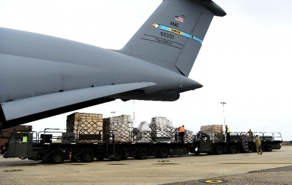 Air mobility Airmen and contractors from the 727th Air Mobility Squadron, RAF Mildenhall, England, push pallets of cargo onto a K-loader off of a C-5 Super Galaxy assigned to the 9thAirlift Squadron, Dover Air Force Base, Delaware, during a medical cargo mission at RAF Mildenhall, England, April 18, 2020. The 727th MS and 9th AS took part in a mission which involved delivering COVID-19 test kits and other equipment to Accra, Ghana, to be distributed throughout the U.S. African Command area of responsibility. (U.S. Air Force photo by Senior Airman Brandon Esau)