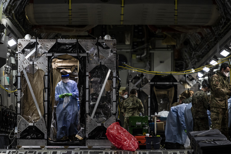 U.S. Air Force Airmen aboard a C-17 Globemaster III begin disinfecting and decontaminating the aircraft after the first-ever operational use of the Transport Isolation System at Ramstein Air Base, Germany, April 10, 2020. The TIS is an infectious disease containment unit designed to minimize contamination risk to aircrew and medical attendants, while allowing in-flight medical care for patients afflicted by a disease—in this case, COVID-19. (U.S. Air Force photo by Staff Sgt. Devin Nothstine)