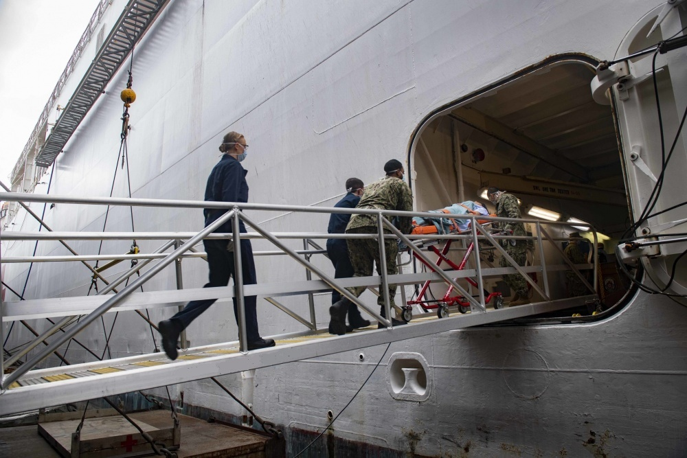 - US Navy Sailors practice patient transfer from the pier onto the hospital ship USNS Comfort (T-AH 20) as they prepare to admit patients in support of the nation's COVID-19 response efforts.