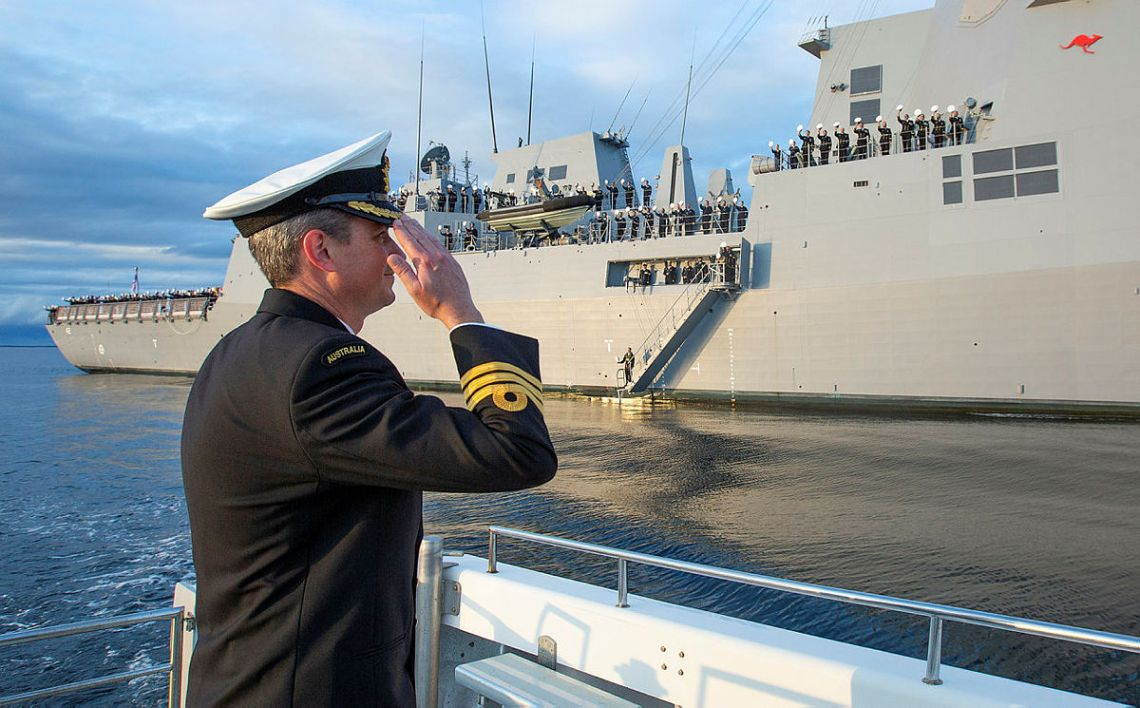 Commanding Officer HMAS Sydney, Commander Edward Seymour, RAN salutes his crew inside Jervis Bay, NSW following the ship's commissioning ceremony at sea. (Photo by Royal Australian Navy/POIS Tom Gibson)